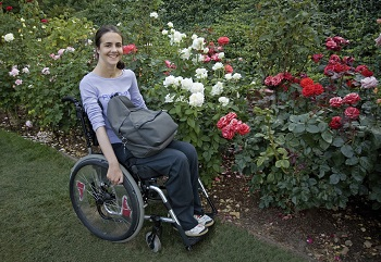 Image of a young woman in a wheelchair in front of a flowers